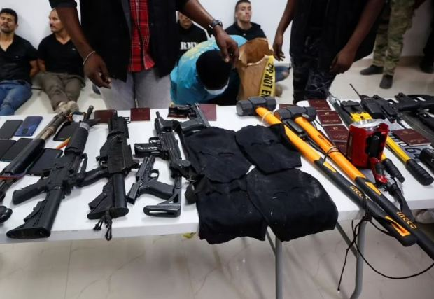 This image has an empty alt attribute; its file name is Weaponry-mobile-phones-passports-and-other-items-are-being-shown-to-the-media-along-with-suspects-in-the-assassination-of-Jovenel-Moise-1.jpg