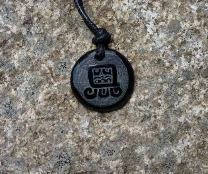 """Maya Nawal Glyph """" Aq'ab'al """" necklace $20.00 Amount Available: 1 The glyph represents the owl. It signifies the sunrise and the sunset, light and dark, a sign of renovation and duality."""