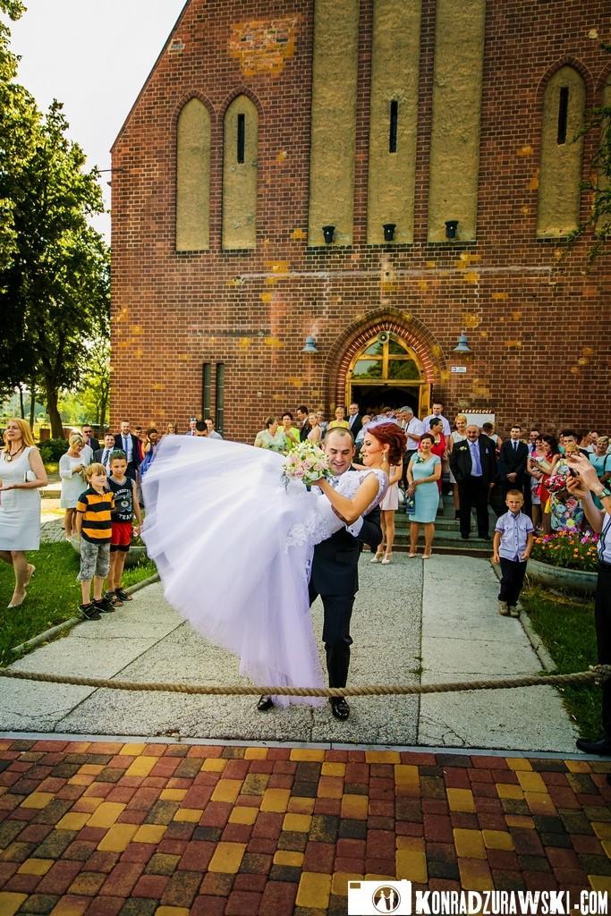 Pan Młody stanął na wysokości zadania i przeniósł Pannę Młodą przez bramę | zdjęcia ślubne Konrad Żurawski