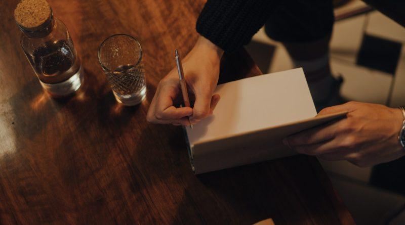 könyvet aláíró kéz