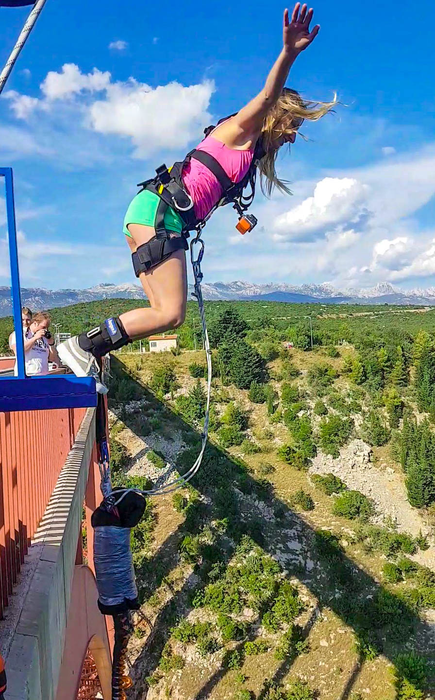 A girl doing Bungee Jumping from Maslenica bridge in Croatia surrounded with Adriatic