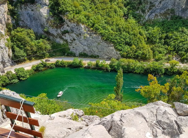 Zipline above the road and green, blue Cetina river