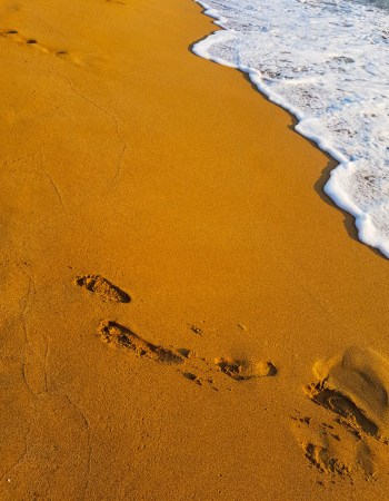 Footsteps in Red Sand Beach in Matala village, Crete island Greece