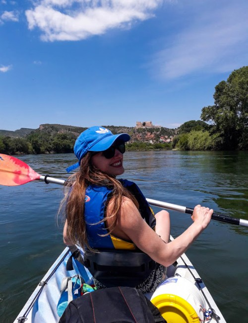 A girl kayaking on the river Ebro with Miravet castle in the distance