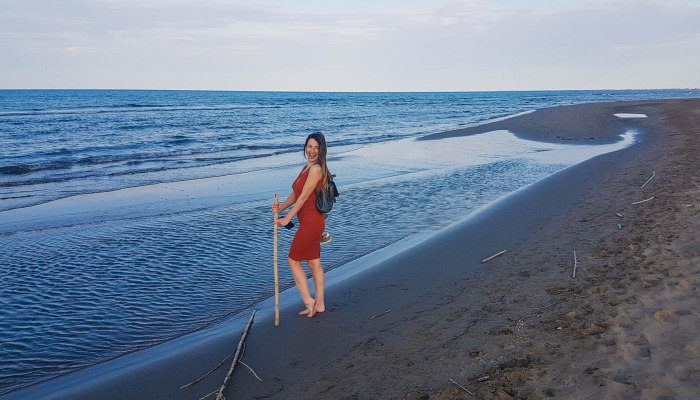 The contrast of the sea and sand with a girl in an orange dress  that smiles