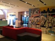 Photograph of the lobby area at The Pod Hotel 51, displaying seating area, artwork and iPads embedded in columns.