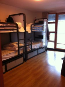 The 6-bed female dorm I stayed in; the photo displays the wooden floors, floor-to-ceiling windows with wooden blinds and bunk beds with privacy screens and under-the-bed lockable storage.