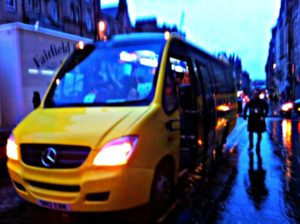 Highland fairytale: silhouette of tour leader Andy wearing his kilt, walking by the side of the Haggis bus
