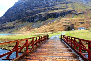 Highland fairytale: wooden bridge to a house in Glencoe