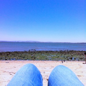 Kindness of strangers: point of view shot of my legs in jeans, laid on the beach, facing the river
