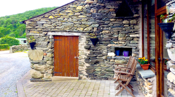 External view of Cosy Cottage, showing the seating area at the front entrance and surrounding green hills