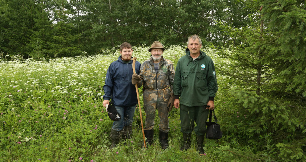 The 3 generations of Pazhetnov men standing in the forest side by side.