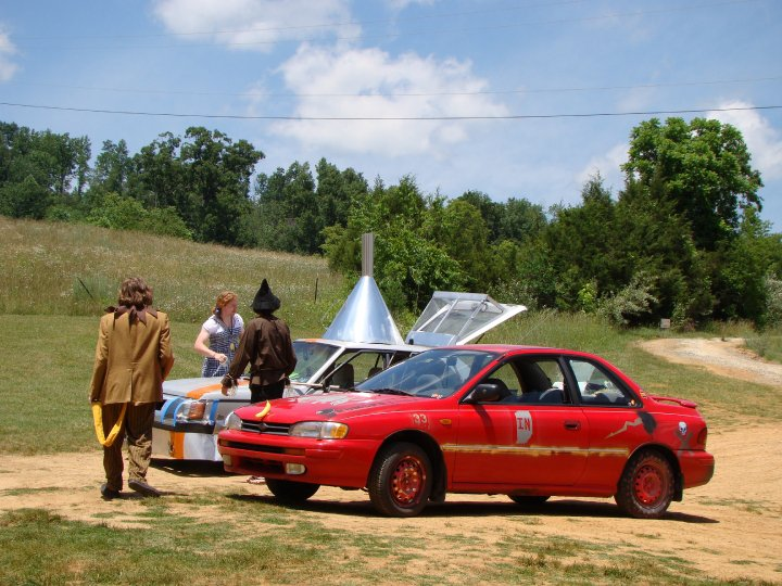 Scavenger hunters dressed as characters from the Wizard of Oz, gather around their customised car which looks like the Tin Man, wearing a pointed tin hat.