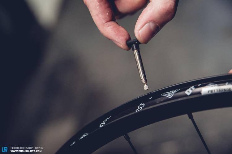Bike mechanic inserting a valve for tubeless tire setup