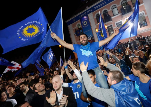 Supporters of ruling Georgian Dream party take part in rally in Tbilisi, Georgia, Saturday, Oct. 8, 2016. Two exit polls in Georgia's parliamentary election show the ruling party in the lead, but the polls differ sizeably on the margin of victory. (AP Photo/Sergei Grits)