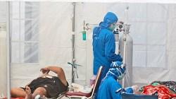 Petugas medis merawat pasien di dalam tenda darurat yang didirikan untuk menampung lonjakan kasus COVID-19, di Rumah Sakit Umum Dr. Sardjito, Yogyakarta, 4 Juli 2021. (AP)