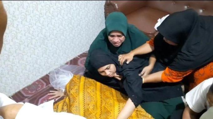 Istri Ustaz Alex menangis di hadapan jenazah suaminya, Minggu (19/9/2021). [Suara.com/ Muhammad Jehan Nurhakim]
