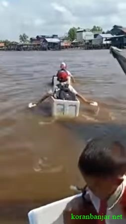 BOCAH SD - Ketiga bocah SD sedang menyeberangi sungai dengan kardus busa. (foto: tangkapan layar video)