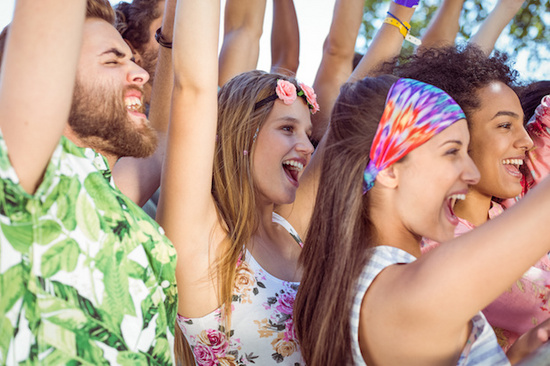 Happy hipsters listening to live music at a music festival