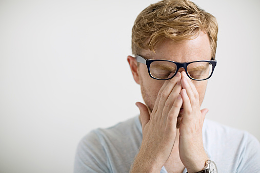 Blonde man rubbing eyes under eyeglasses