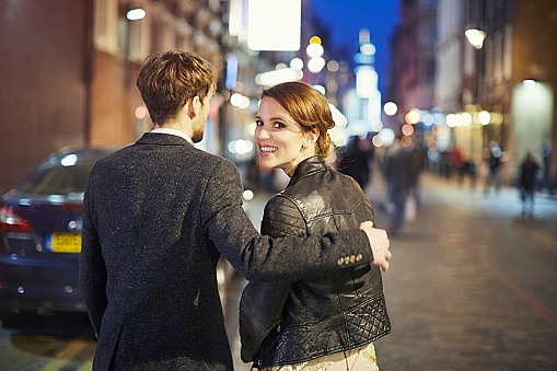 Couple on street at night, London, England