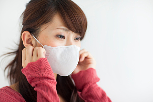 Young woman wearing mask, white background