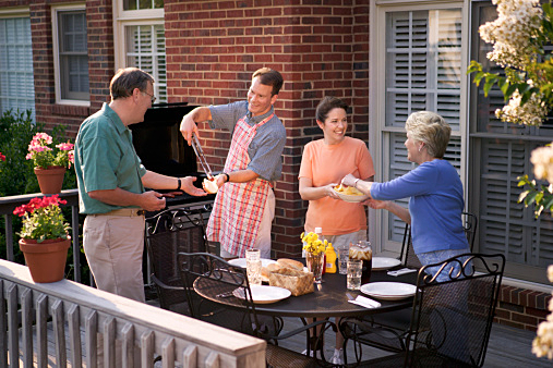 Two couples pass food while having a cookout on the back porch