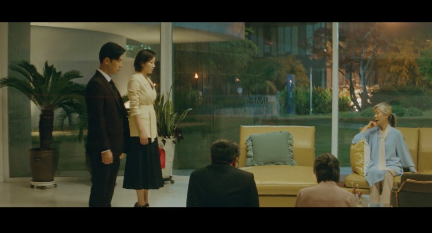 Ga Gyeong berdiri bersama suaminya saat kedua orang tuanya berlutut di hadapan sang ibu mertua.