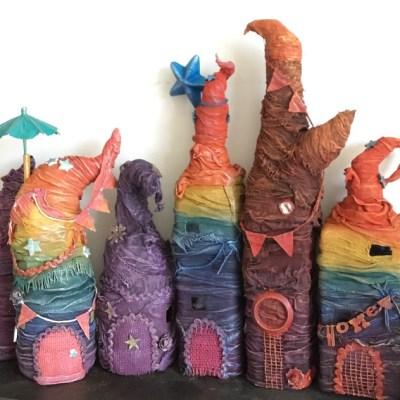 Row of Powertex fairy houses with rainbow stripes