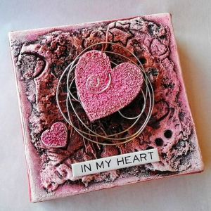 Mixed media art of pink hearts layered on a textured canvas