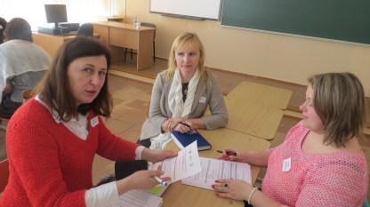 Jolita, Kristina ir Renata studijuoja projekto dokumentus.
