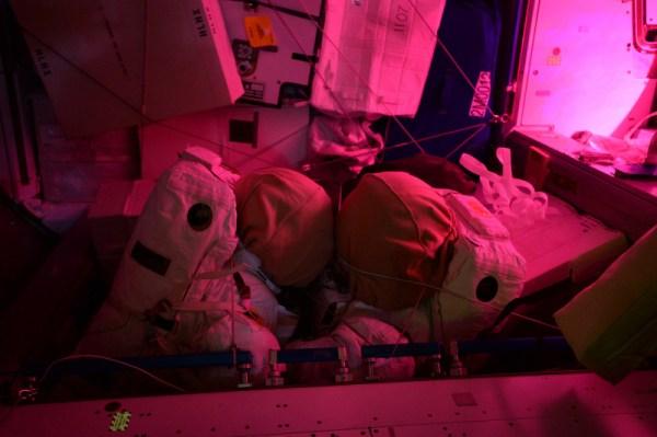 Intimní atmosféra vesmírné stanice: v noci se tyto dva skafandry společně proplétají… tajemné růžové světlo skleníku v Columbu na scéně jen přidává.
