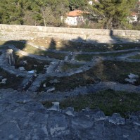 View down terraces, broken stone markers, and surrounding vegetation.