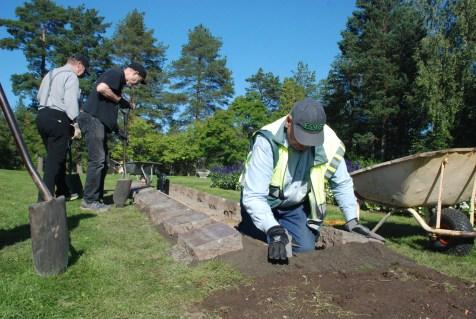 Jouko Tolvanen (etualalla) valmisteli hautakivien välin kunnostusta.