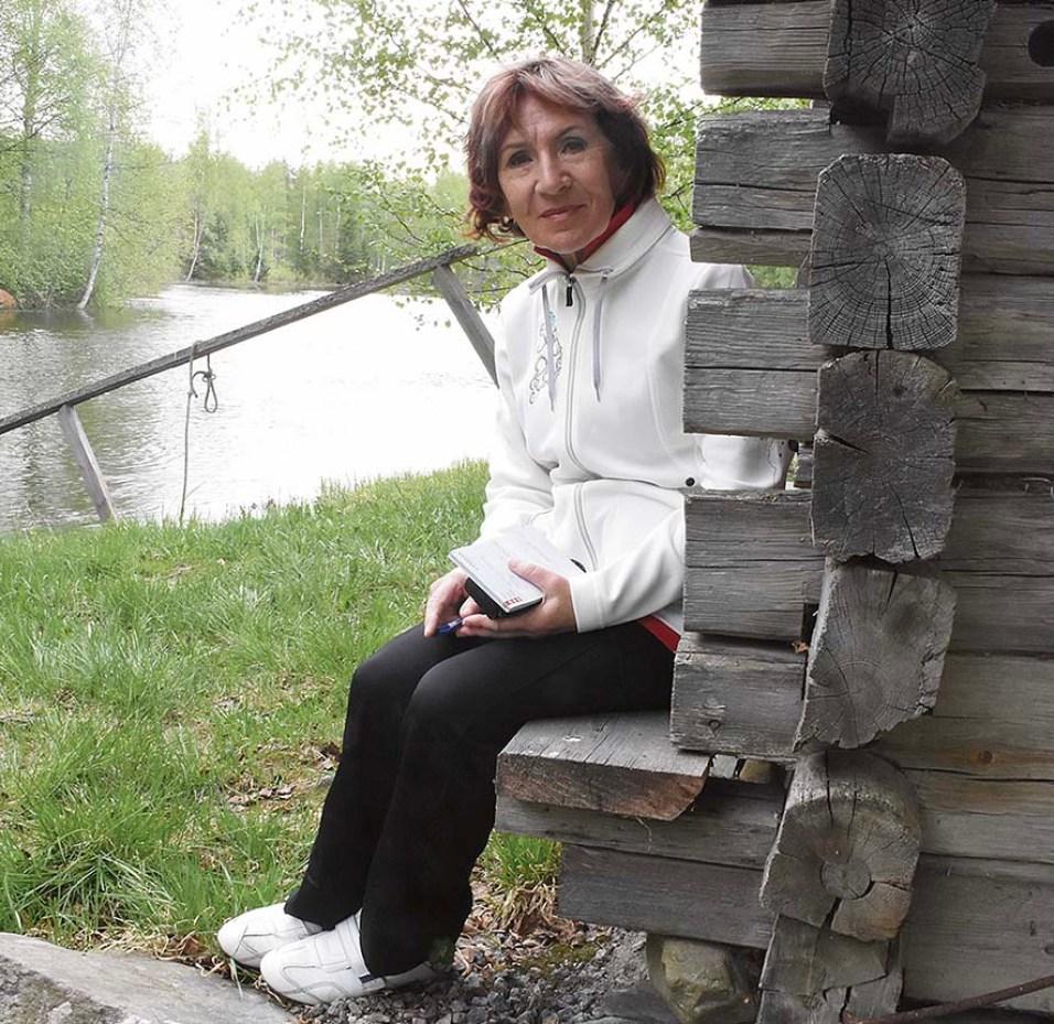 Pirkko Mutanen istuu savusaunan sivupenkillä, josta aukeaa hieno maisema joelle.