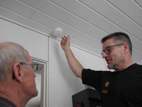 Paavo Karvinen (oik.) neuvoo Aulis Huikuria siirtämään palovaroittimen vähintään 30 senttimetrin päähän seinästä. Seinää pitkin nouseva savu tekee katon rajassa mutkan ohi varoittimen.