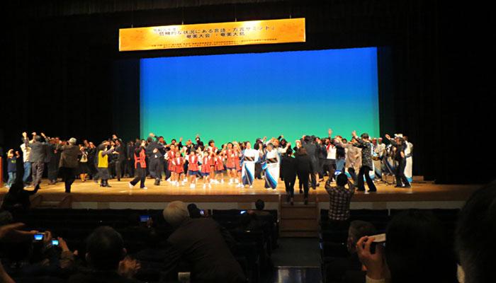 会場から舞台に飛び入りし,「八月踊り」で盛り上がる人々