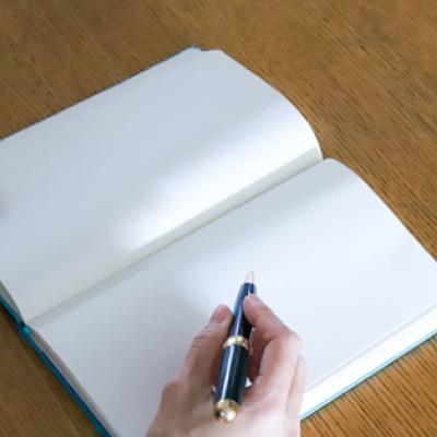 ペンでノートに書き込もうとしている