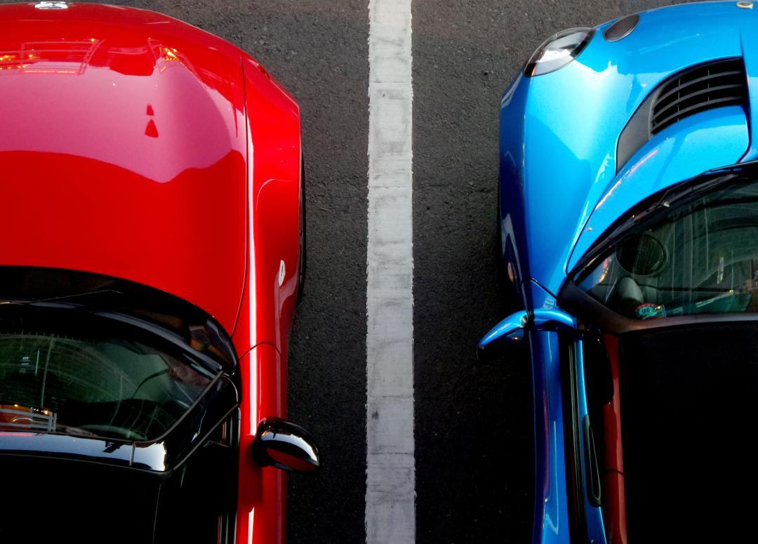 Une voiture bleue et une voiture rouge dans un parking