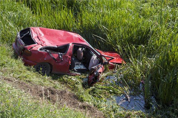 Patakba borult, majd a tűzoltók által a kerekeire állított autó a 75-ös főút 27-es kilométerénél, Pölöske és Zalaszentmihály között 2014. július 20-án. Az autó a hídfőnek ütközött, majd a patakba borult. A kocsiban utazók egyike a vízbe fulladt, a másik utas, egy gyerek beszorult a járműbe, őt a tűzoltók szabadították ki. MTI Fotó: Varga György