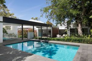 Pre-war-house-extension-features-a-raised-dining-area-and-poolside-deck