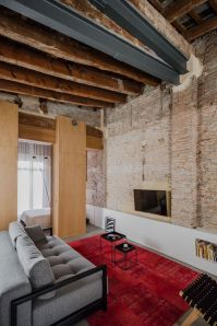 Musico-apartment-introduces-a-red-area-rug-in-the-lounge-space