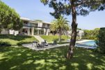 St-Tropez-Residence-features-an-outdoor-lounge-shaded-by-tropical-trees