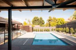 Upside-Down-House-features-a-backyard-pool-framed-by-fences