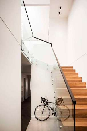 Upside-Down-House-features-a-wood-staircase-with-sleek-glass-railings