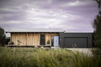 Golf-Course-House-with-wood-clad-exterior-walls-and-a-black-garage