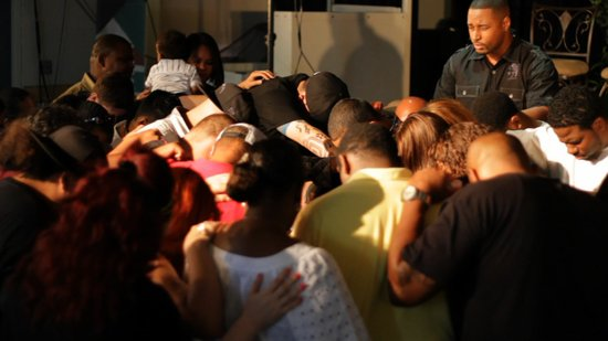 Pastor Vic looks on as members of The Body Church pray together.
