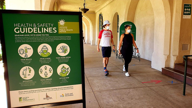 Pedestrians wearing face masks walk through Balboa Park. August 1, 2020.