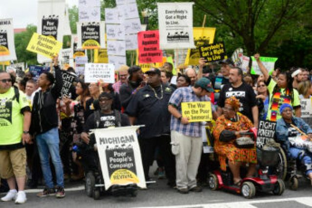"""Poor People's Campaign March To The Capitol 2018. Photo by Stephen Melkisethian*  A large multi-racial crowd, hundreds of people, with a woman in colorful robe in a scooter and two other wheelchair users  at the front.  Among the many signs are some that read """"Poor People's Campaign"""", """"Disability plus Ableism equals Poverty"""", and """"Systemic Racism is Immoral."""""""