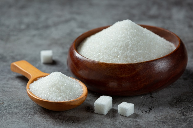 sugar in a wooden bowl and spoon